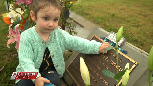 Mr and Mrs Parnell's two-year-old daughter Heidi at her father's grave.
