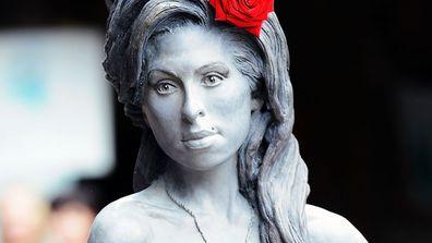 """<p></noscript> Una estatua de bronce de tamaño natural de Amy Winehouse, con una rosa roja en su peinado de colmena, fue presentada en Londres para celebrar el 31 cumpleaños de la cantautora británica.  (Getty) </ p> </p> <p> <b>  Historia de la AAP </b> </p> <p>""""/></p></div> <div class="""