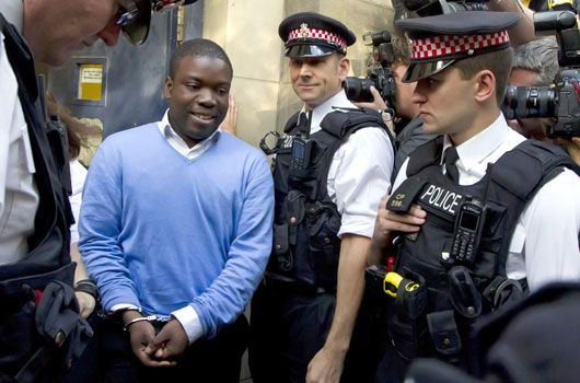 Alleged rogue trader Kweku Adoboli (centre) walks into a security van after appearing at the City of London Magistrates Court. (AAP)
