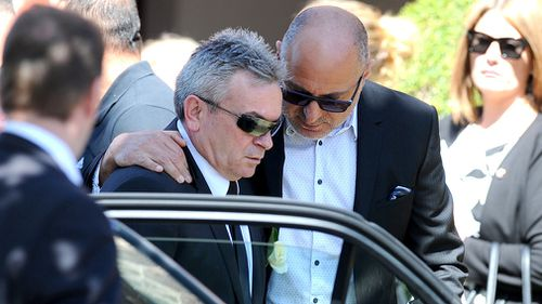 Mr Ristevski being comforted by a friend at his wife's funeral. (AAP)