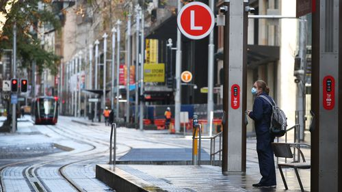 A frontline worker awaits the a tram on George Street in Sydney amid the city-wide lockdown. Sydney lockdown