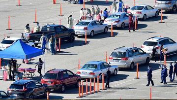People arrive for their COVID-19 vaccine at the Auto Club Speedway in Fontana, California on February 2, 2021 - The first Covid-19 vaccine 'super site' in San Bernadino County - California's largest county - opened on Tuesday.