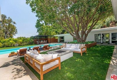 The backyard features a stunning Coral tree and lush landscaping.