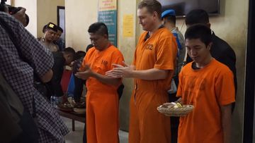 Van Iersel even managed to crack a smile as he was served his meal at Denpasar police station, where the pair is being held in the lead up to their court case.