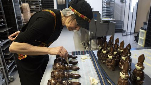 Genevieve Trepant decorates chocolate rabbits at her shop, Cocoatree, in Lonzee, Belgium