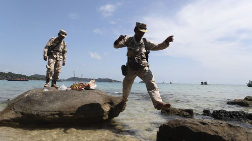 Cambodia soldiers leap rocks after offering prayers in hopes of finding British national Amelia Bambridge on the shore of Koh Rong island.