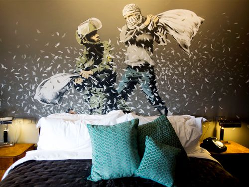 "A Banksy wall painting showing Israeli border policeman and Palestinian in a pillow fight is seen in one of the rooms of ""The Walled Off Hotel"". (AAP)"