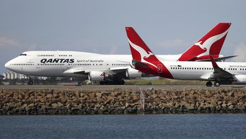 Qantas planes taxi on the runway at Sydney Airport.