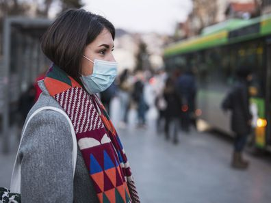 Woman in face masks waits for a bus