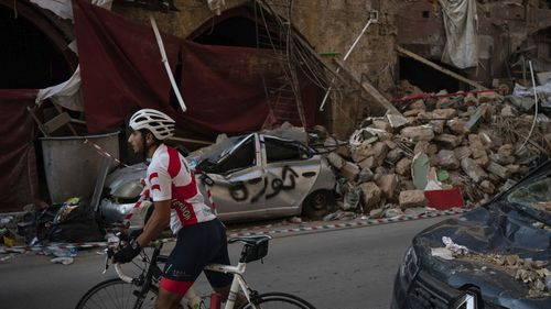 A cyclist rides past destroyed buildings and cars in a neighbourhood near the site of last week's explosion that hit the seaport of Beirut, Lebanon, Tuesday, Aug. 11, 2020