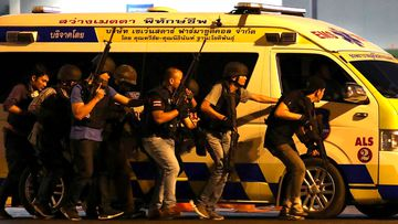 Thailand security forces take cover behind an ambulance as they chase a shooter thought to be hiding in a shopping mall after a mass shooting in Thailand.