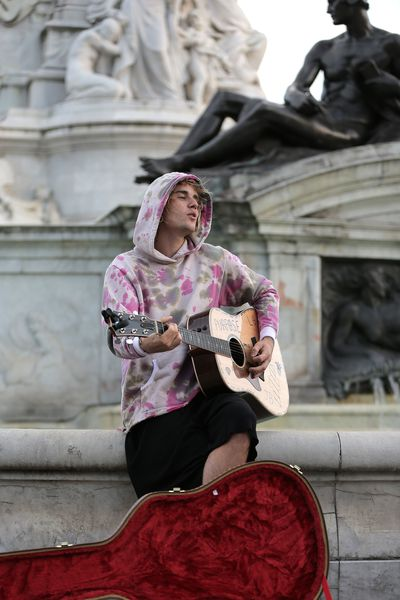 The 24-year-old performed in a pink camouflage hoodie while sitting atop the Victoria Monument outside the palace.