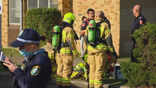 Police and firefighters outside a unit in Malabar following a fire.