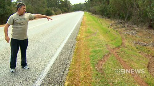 Witness Phil Ferraro shows where the suspected victim of an attempted carjacking turned around before rolling. (9NEWS)