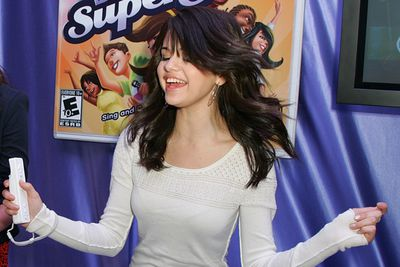 Not shy of showing her goofy side, Selena jumps around whilst playing video game. <br/>