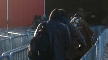 Minor migrants walk the closures towards the registration center in the jungle of Calais in Calais, France, on 25 October 2016. (AFP)