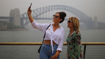 Duo take selfie outside Sydney Harbour Bridge as smoke shrouds the city.