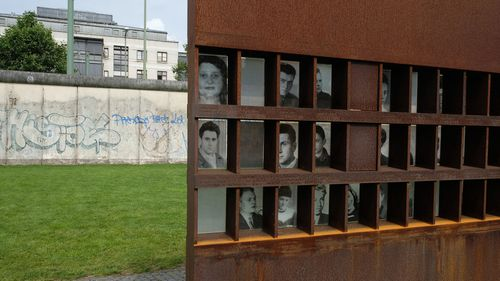 At the Berlin Wall Memorial the Window of Remembrance shows photos of victims of the wall who died while trying to escape the communist state between 1961-1989 during the Cold War seen on July 16, 2017 in Berlin, Germany. A section of the Berlin Wall is seen behind Bernauer Straße. (Photo by Kaveh Kazemi/Getty Images)