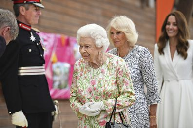 Britain's Queen Elizabeth II , centre, Camilla, the Duchess of Cornwall and Kate, the Duchess of Cambridge, attend an event in celebration of 'The Big Lunch 'initiative, during the G7 summit in Cornwall, England, Friday June 11, 2021. (Oli Scarff/Pool Photo via AP)