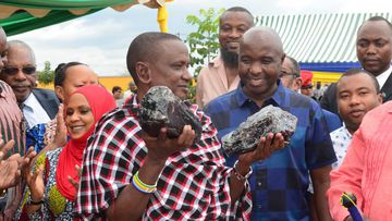 Saniniu Laizer holding the two massive gemstones he dug up.