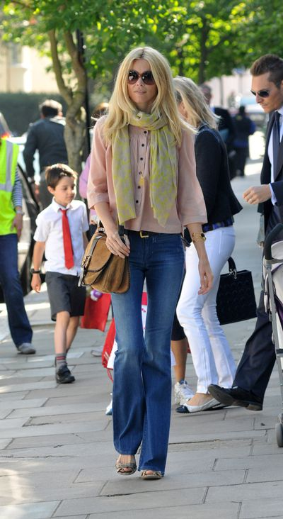 Coachella-worthy flared denim jeans and a pastel scarf are supermodel Claudia Schiffer's school run edit in Notting Hill.