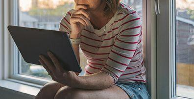 Woman sitting at home on computer sad