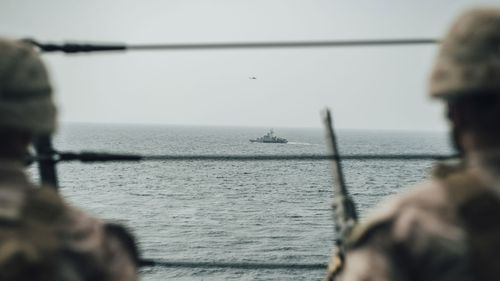 US Marines observe an Iranian fast attack craft from the San Antonio-class amphibious transport dock during a Strait of Hormuz transit.