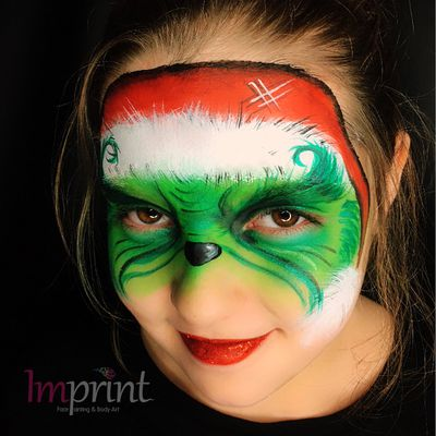 A bright red lip complements this festive face paint