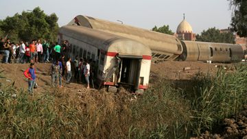 People gather at the site where train carriages derailed in Qalioubia province, north of Cairo.