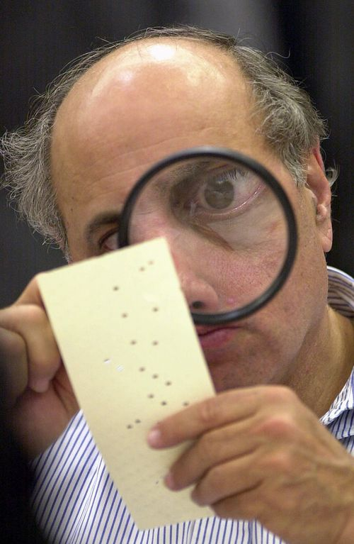 In another of Diaz's iconic photographs, canvassing board member Judge Robert Rosenberg uses a magnifying glass to examine a disputed election ballot. Picture: Alan Diaz / AP
