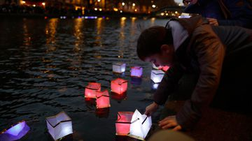 Floating lanterns are placed on the Canal St Martin to commemorates the anniversary of the Paris terrorist attacks. (AFP)