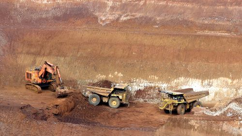 A digger and two heavy trucks on site at Mount Weld mine in Western Australia.