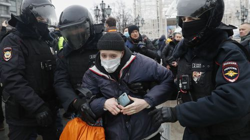 Police detain a protester during a protest against the jailing of opposition leader Alexei Navalny in Moscow, Russia, Saturday, Jan. 23, 2021