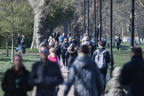 People are seen walking on Clapham Common on March 22, 2020 in London, despites social distancing warnings.