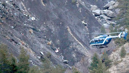 A rope hangs from a rescue helicopter flying past debris of the Germanwings passenger jet. (AAP)
