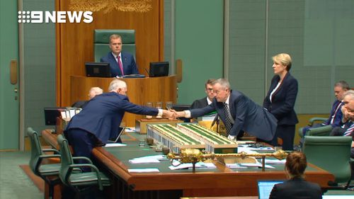 Malcolm Turnbull and Bill Shorten shake hands in a show of unity against Senator Anning's comments last night.