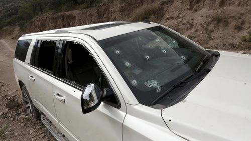 A bullet-riddled vehicle that members of LeBaron family were traveling in sits parked on a dirt road near Bavispe, at the Sonora-Chihuahua border, Mexico,.
