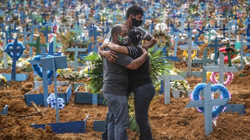 Mourners embrace one another at a graveyard in Manaus, Brazil.