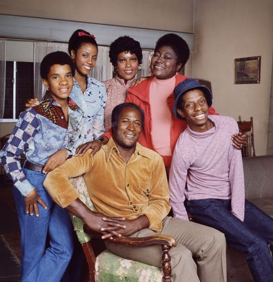 Good Times cast members (left to right) Raplh Carter (as Michael Evans);  BernNadette Stanis (as Thelma Evans Anderson);  Ja'net DuBois (as Willona Woods);  John Amos (as James Evans);  Esther Rolle (as Florida Evans)  and Jimmie Walker (as James Evans, Jr. / J.J.). 1975. Copyright CBS Worldwide Inc. All Rights Reserved. Credit: CBS Photo Archive.