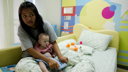 Thai surrogate mother Pattaramon Chanbua (L) holds her baby Gammy, born with Down Syndrome. (NICOLAS ASFOURI/AFP/Getty Images)