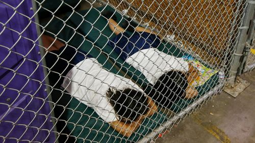 Two young migrant detainees sleep in a holding cell in 2014. Picture: AP