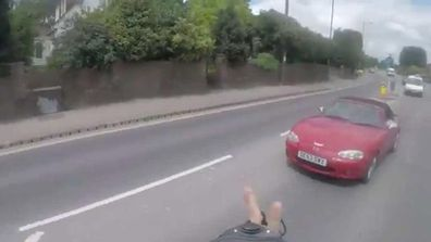 """<p _tmplitem=""""1"""">A British cyclist who cut off a car then collided with a roadside wall in full view of the driver he just flipped off.</p><p _tmplitem=""""1""""> The unidentified man captured his own embarrassing tumble on a helmet camera while riding along London Road in the south east state of Hampshire – even uploading it online overnight. </p><p _tmplitem=""""1""""> In the footage, the rider appears to be rushing as he pedals furiously along the busy M3 motorway from Surrey to Hampshire. </p><p _tmplitem=""""1""""> While overtaking a slower cyclist, the man darts outside of the marked bike lane and into a the path of a car traveling faster. </p><p _tmplitem=""""1""""> The driver sounds the horn and in reply, the cyclist turns his head – along with the camera – to show him throw two fingers into the air and tell the motorist to """"f--- off"""".</p><p _tmplitem=""""1""""> These prove vital seconds where he should have been looking at the road, with the man turning back just in time to capture the nasty tumble. </p><p _tmplitem=""""1""""> It is not clear if he suffered any physical injuries, although his ego almost certainly copped a bruising. </p><p _tmplitem=""""1""""></p>"""