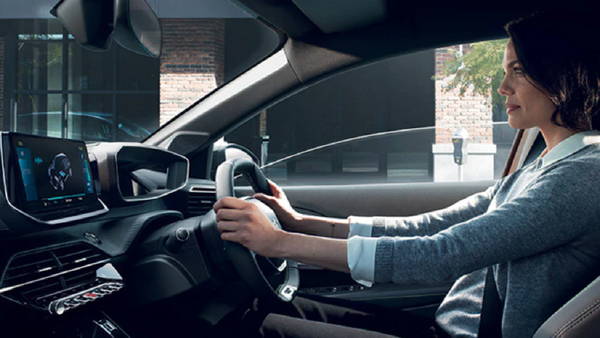 Woman holding the steering wheel of car.