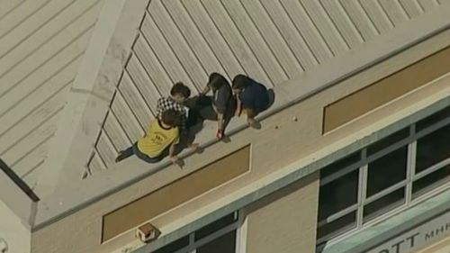The four protesters on top of Tony Abbott's Manly electoral office. (9NEWS)