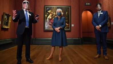 Chair of the Board of Trustees Tony Hall (L) gives a speech as Camilla, Duchess of Cornwall (C) and National Gallery Director Gabriele Finaldi look on during a visit to the recently reopened National Gallery on July 28, 2020 in London, England