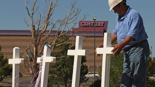Greg Zanis placing two of the twelve crosses he made for a makeshift memorial to the victims of a mass shooting at the Century 16 movie theatre on July 22, 2012 in Aurora, Colorado. (AFP)