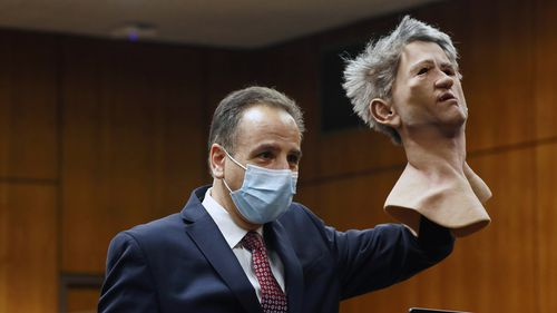Deputy District Attorney Habib Balian held a rubber latex mask, worn by Robert Durst when police arrested him.