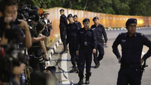 Singapore police stand guard in front of members of the media outside the Capella Hotel. (AAP)