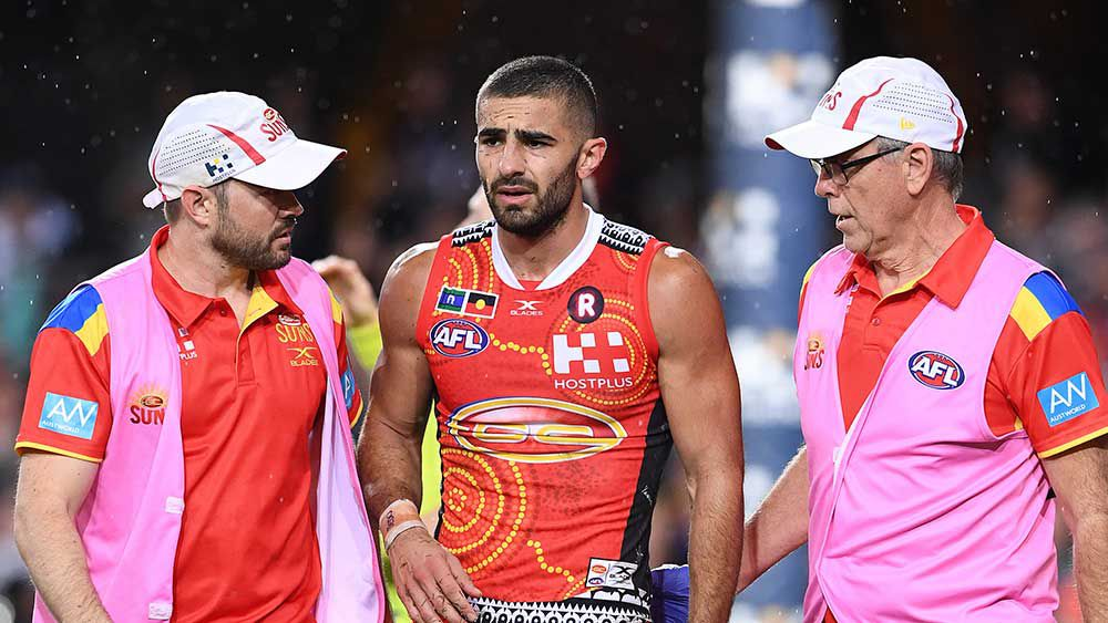 Adam Saad gets looked at by the Suns trainers. (AAP)