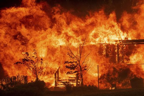 Flames consume a home as the River Fire tears though Lakeport, Calif., on Tuesday, July 31, 2018. (AP Photo/Noah Berger, File